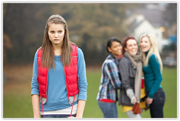 Image of a saddened girl with gossiping girls in the background