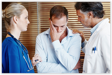 Image of patient being consoled by doctor and nurse